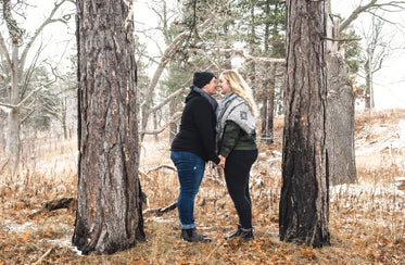 smiling couple stand nose to nose between two trees