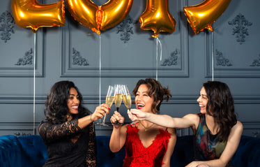 smiling friends clink champagne glasses at midnight