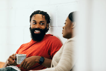 smiling man holds cup of tea