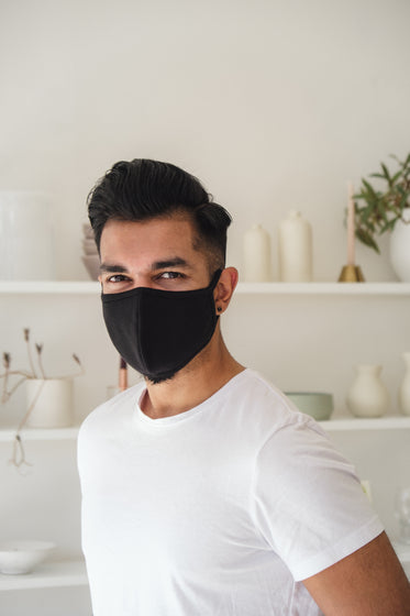 smiling man in black cloth face mask