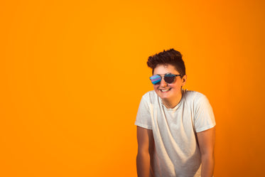 smiling person in sunglasses and white tshirt
