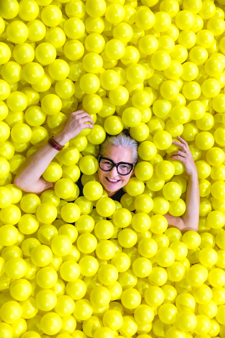 Smiling Senior In Yellow Ball Pit