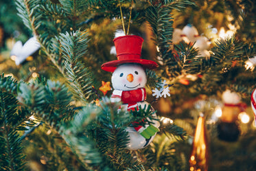 smiling snowman ornament on tree