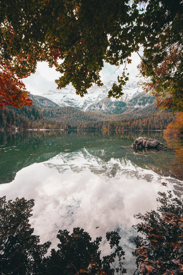snow covered mountains reflect on the water by a fall forest