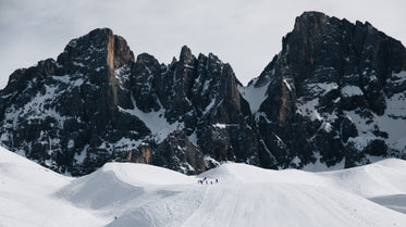 snow covered mountains with hikers