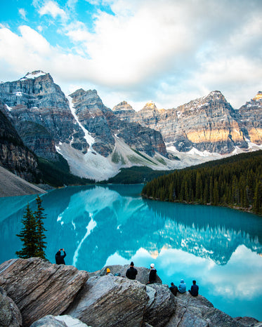 snowy mountains reflect in a blue pond