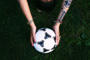 soccer ball in hands on grass