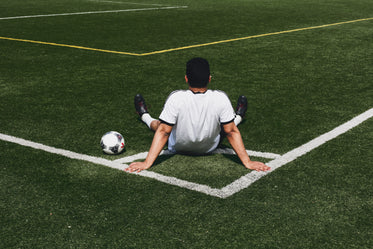 soccer player sits at field corner