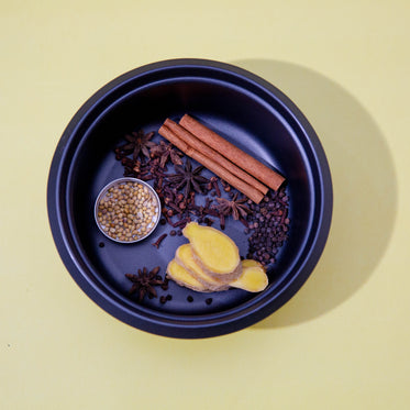 spices lay in a blue bowl against a yellow background