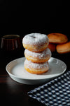 stack of doughnuts with white powered tops on a plate