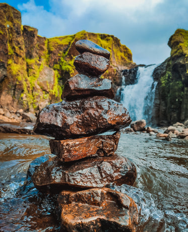 stack of wet rocks with a waterfall behind