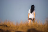 standing in tall brown grass away from the camera