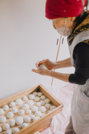 standing over wooden box of small balls of dough