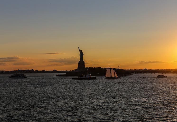 Statue Of Liberty Lit By Sunset