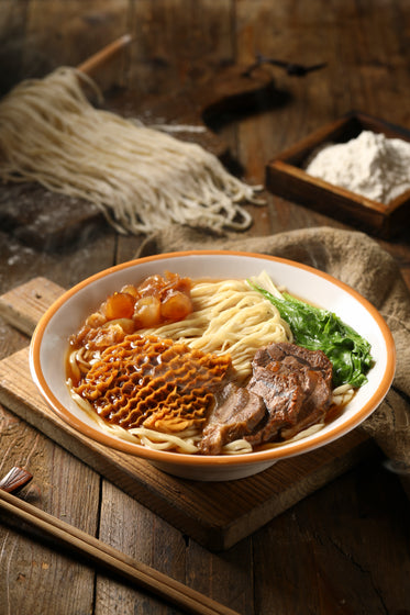 Steaming Bowl Of Noodle Soup On A Wooden Surface