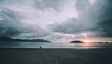 still beach at sunset with person crouching
