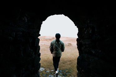 stone archway frames a person walking to beach