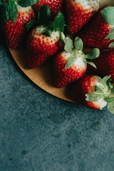 strawberries on a wooden plate over black surface