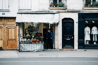 street with a fruit stand and a person in a facemask