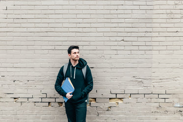 student leaning against brick wall