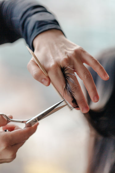 stylist trimming a woman's hair