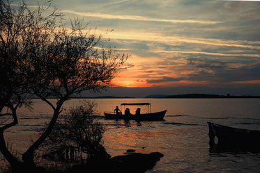 sun sets and silhouettes a boat on evening water