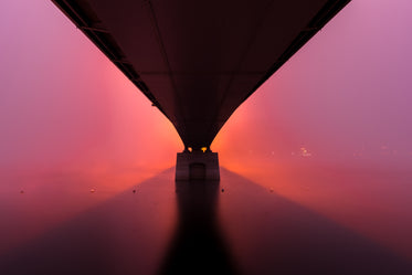 sunrises under a stone bridge creating a pink sky