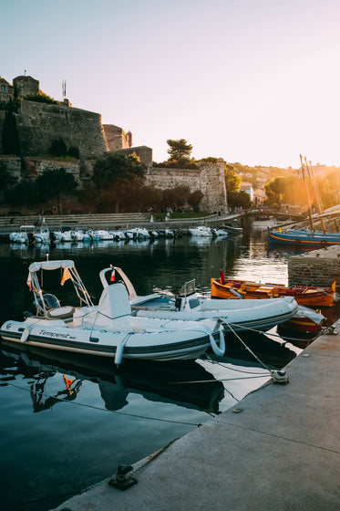 sunset over bastions and boats of a marina