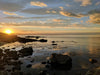 sunset over water by rocky shore