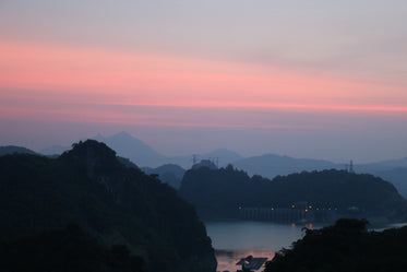 sunsets behind large tree covered hills and body of water