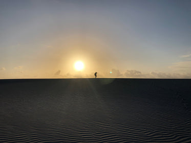 sunsets in the desert silhouetting a person