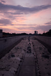 sunsets on a large cement pathway lined with flowers