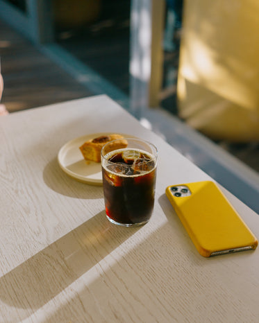 table with iced coffee and a cell phone face down
