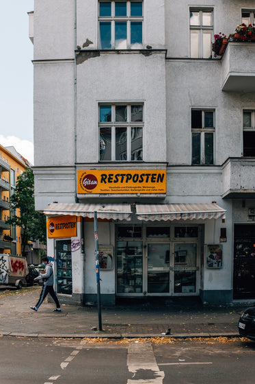 tall building with an orange sign that says restposten
