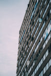 tall grey building with lines of reflective windows