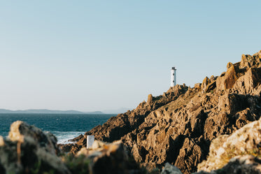tall lighthouse on sharp rocky shoreline against blue water