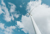 tall modern windmill against a blue sky with fluffy clouds