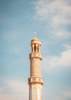 tall thin tower with a round roof against a blue sky
