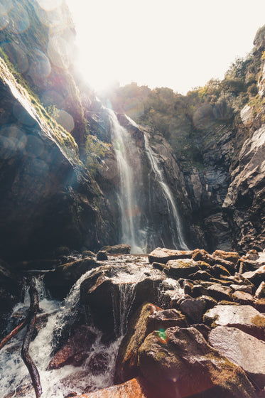 tall waterfall over large rocky surface