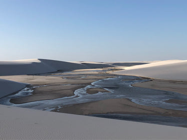 tanned sand dunes surrounded an open reservoir