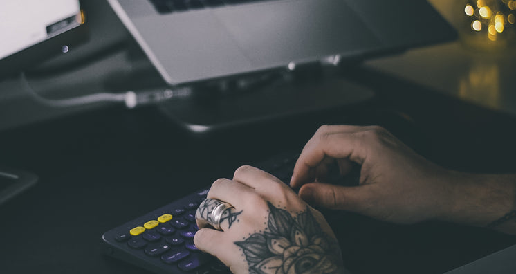 Tattooed hands Typing On Office Keyboard