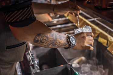 tattooed person holding a glass with ice over a bar well