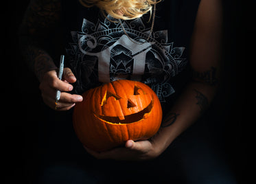 tattooed woman carving halloween pumpkin