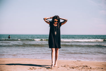 tattooed woman on beach with toes in the sand