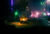 taxi cab drives down empty street at night