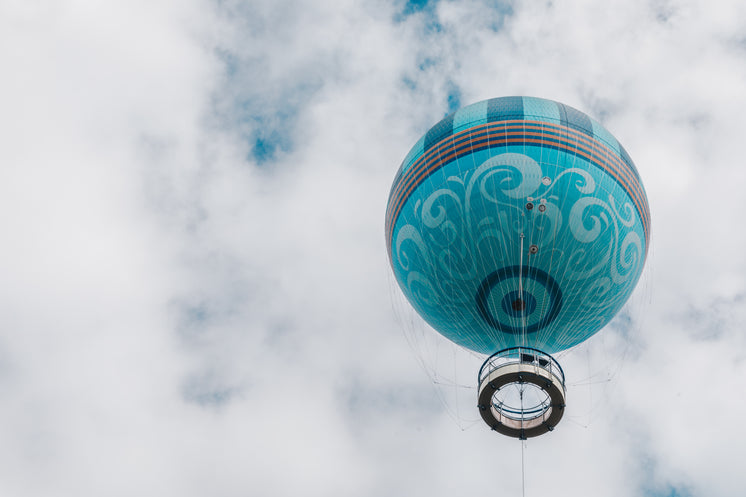Teal Hot Air Balloon Floats Up Into White Puffy Clouds