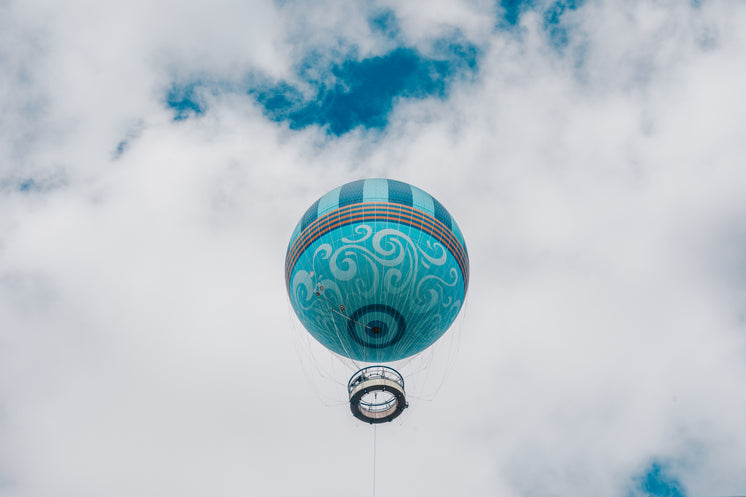 Teal Hot Air Balloon Framed By Puffy White Clouds and Blue Sky