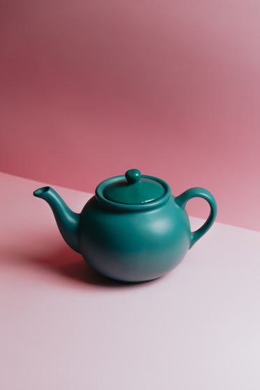 teapot against a lit pink background