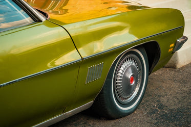 the front side of an olive green classic car