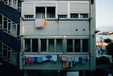 the grey face of an apartment block draped in clothes lines